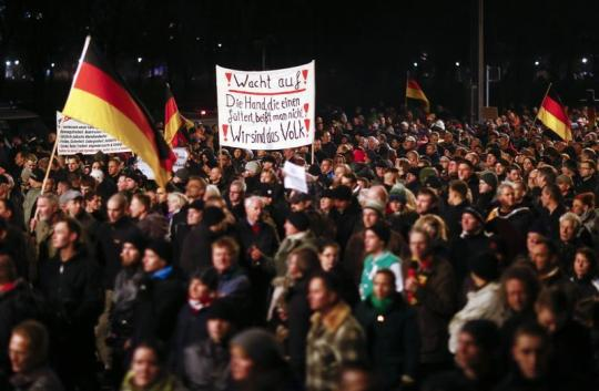 Participants hold German national flags and a banner during a demonstration called by anti-immigration group PEGIDA in Dresden